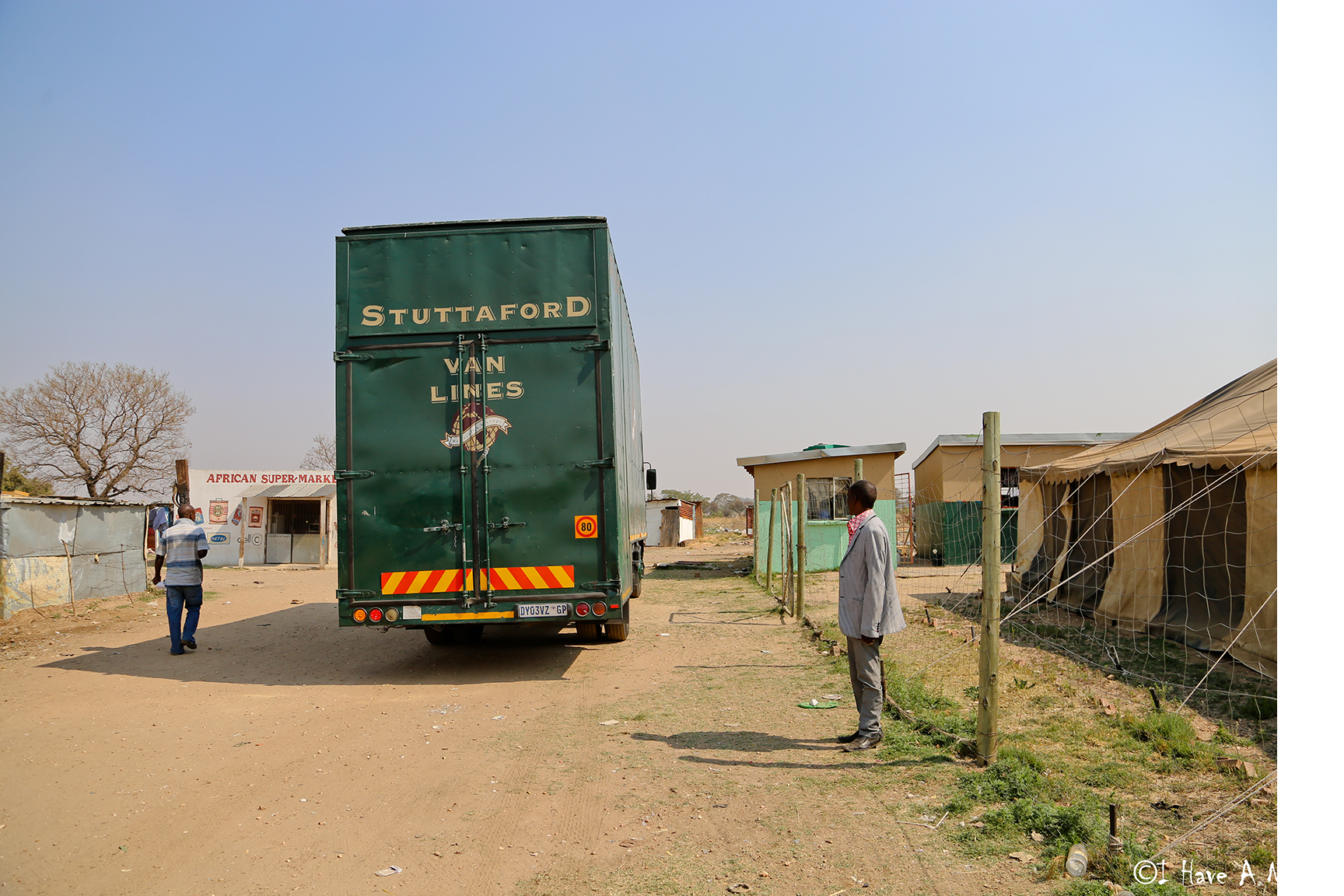 Green truck driving through a township.